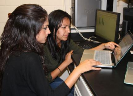 two women studying a laptop screen