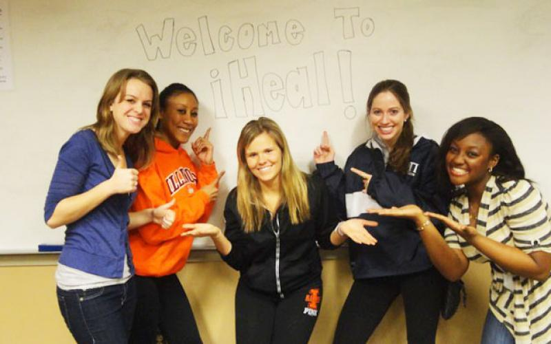 Three students standing in front of a bulletin board with Welcome to iHeal written on it